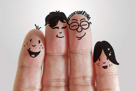 happy family with painted smiley on human fingers