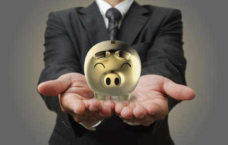 Businessman shows a piggy bank