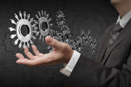 Business team cooperation with  wheels made of gears or cogs as human worker symbols