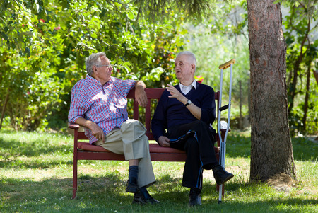 Two retired men sitting on bench in park and talking
