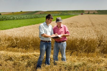 Photo pour Peasant and businessman looking at notebook on wheat field - image libre de droit