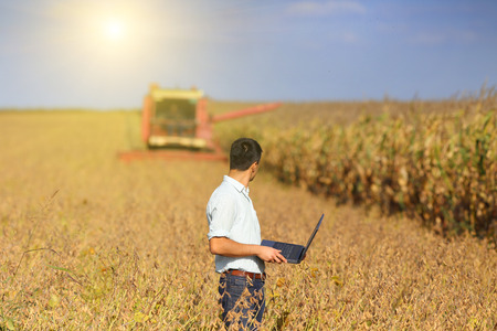 Young landowner with laptop supervising soybean harvesting work