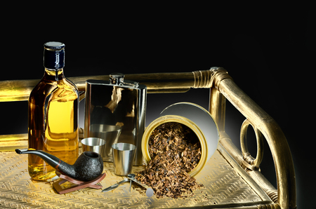 Smoking pipe, tobacco, whiskey and hip flask on bamboo shelf