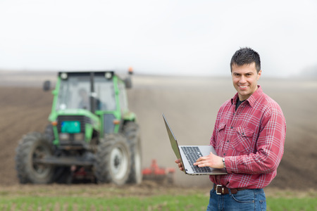 Photo pour Young landowner with laptop supervising work on farmland, tractor in background - image libre de droit