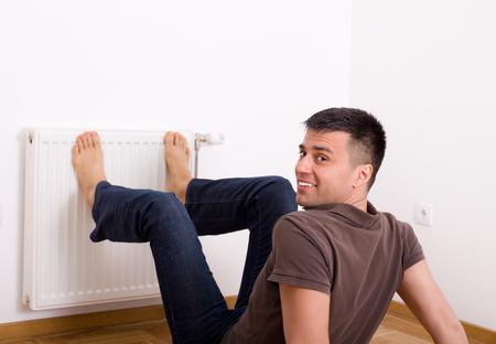 Young man heating his bare feet on radiator on wall