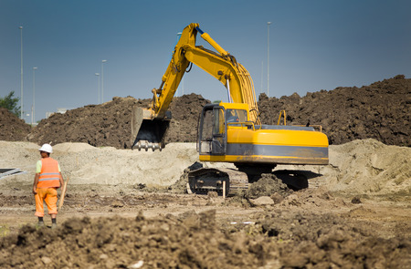 Photo pour Excavator digging and moving earth at construction site - image libre de droit