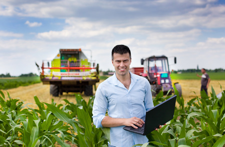 Young attractive farmer with laptop standing in corn field tractor and combine harvester working in wheat field in background