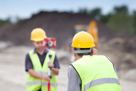 Photo for Surveyor engineers working with theodolite on road construction site - Royalty Free Image