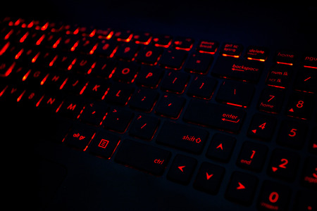 Red backlight on the modern keyboard of gaming laptop in the dark
