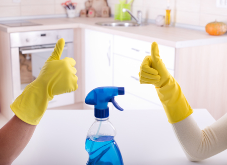 Close up of two workers gesturing ok sign after good job of cleaning in the kitchen