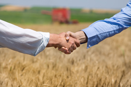 Photo pour Close up of two businessmen shaking hands on the farmland. Combine harvester working in background - image libre de droit