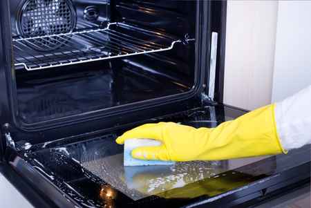 Photo pour Close up of female hand with yellow protective gloves cleaning oven door - image libre de droit