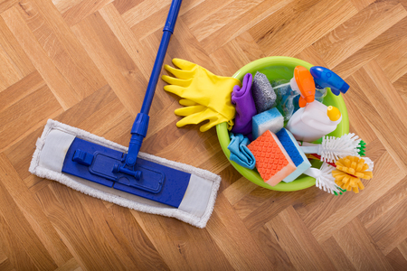 Foto de Top view of mopping stick and washbasin full of cleaning supplies and equipment on the parquet - Imagen libre de derechos