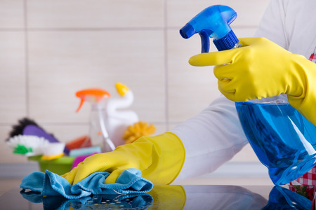 Photo for Close up of human hand with protective gloves cleaning induction hob with rag. Cleaning supplies in background - Royalty Free Image