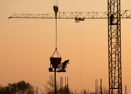 Photo pour Silhouette of construction worker on the crane at sunset - image libre de droit