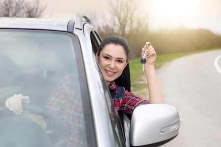 Young pretty woman showing keys through car window and expressing happiness, on the road