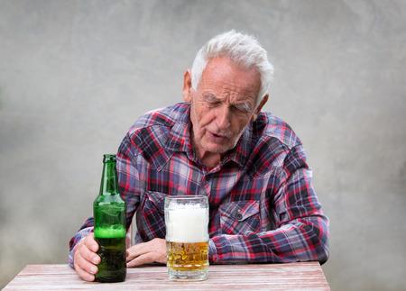Foto de Senior drunk man sitting at table with beer bottle and mug in front of him - Imagen libre de derechos