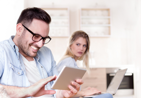 Foto de Young couple having issues in relationship. Man holding tablet and smiling and girlfriend look jealously in background - Imagen libre de derechos