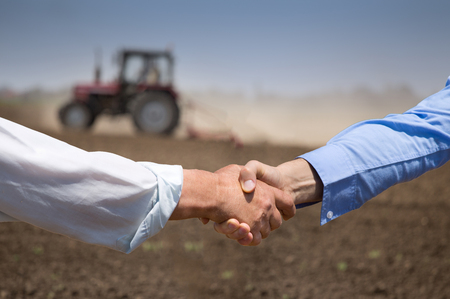 Photo pour Two businessmen shaking hands in field with tractor working in background. Agribusiness concept - image libre de droit