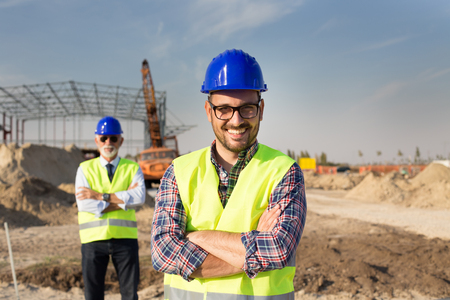 Photo pour Portrait of satisfied and confident engineer with helmet and vest on building site - image libre de droit