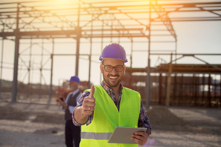 Photo pour Portrait of satisfied engineer holding tablet and showing thumb up on building site - image libre de droit