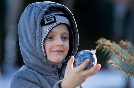 Photo pour Cute young boy looking at christmas decoration hanging on fir tree on cold winter day with snow - image libre de droit