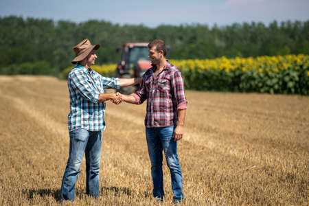 Two farmers shaking hands in wheat field during harvest, with tractor working in background