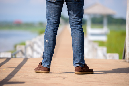 Legs of backpackers or Hikers on the river bridge as a tourist attraction.