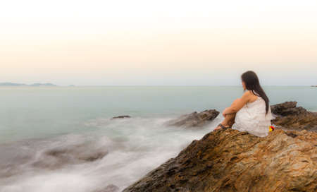A sad and depressed woman sitting by the ocean deep in thought.