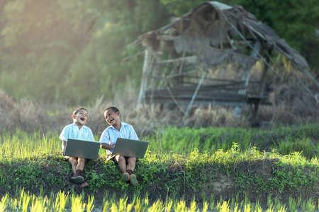 Photo pour Happy boy using a laptop outdoors - image libre de droit