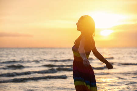 Photo pour Enjoyment - free happy woman enjoying sunset. Beautiful woman in white dress embracing the golden sunshine glow of sunset with arms outspread and face raised in sky enjoying peace, serenity in nature - image libre de droit