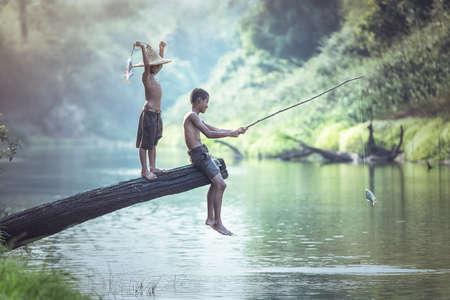 Photo pour Boy fishing at the river - image libre de droit