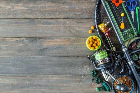 Foto de Fishing tackle - fishing spinning,Carp fishing rods, hooks and lures, fishing rod, fishing line, coil on darken wooden background - Imagen libre de derechos