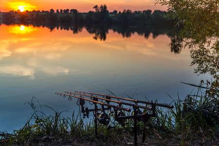 Photo pour Fishing adventures, carp fishing. Angler, at sunset, is fishing with carpfishing technique. Camping on the shore of the lake.Carp Fishing Sunset - image libre de droit