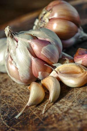 Foto für Organic garlic,Closeup garlic on wooden texture on for cooking on dark background, concept healthy lifestyle.Fresh peeled garlics and bulbs. - Lizenzfreies Bild