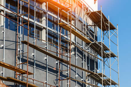 Foto de Extensive scaffolding providing platforms for work in progress on a new apartment block, Tall building under construction with scaffolds, Construction Site of New Building - Imagen libre de derechos