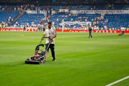 Man with lawn mower cutting grass on the football field on the Santiago Bernabéu stadium, Madrid, Spain 2018-08-12