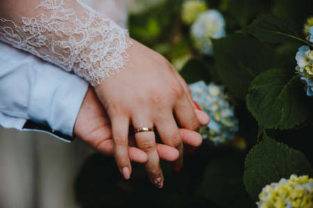 Photo pour Young married couple holding hands, ceremony wedding day - image libre de droit