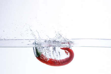 hot chili pepper in the water. splash of water and fruit floating in it.