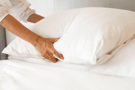Photo pour Female Hand set up white bed sheet in bedroom - image libre de droit