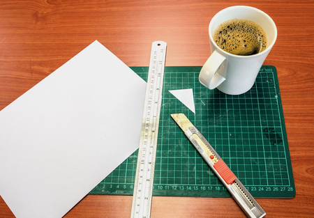 Green Cutting mats , notebook , pen , cup of coffee on the wood