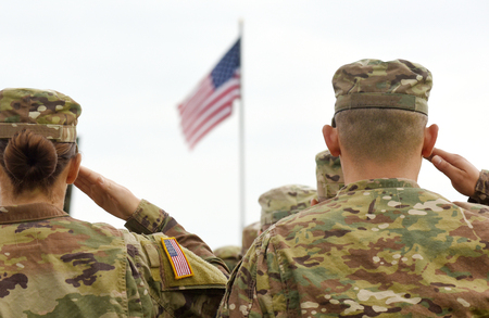 Foto per American Soldiers Saluting US Flag - Immagine Royalty Free