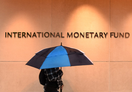 Washington, DC - June 04, 2018: Pedestrian with an umbrella near International Monetary Fund, IMF Headquarters 2 Building (HQ2) in DC.