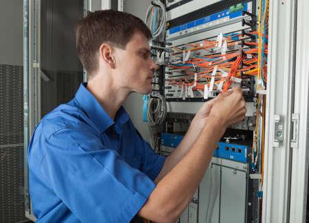 senior  Network engineer in server room wokinig