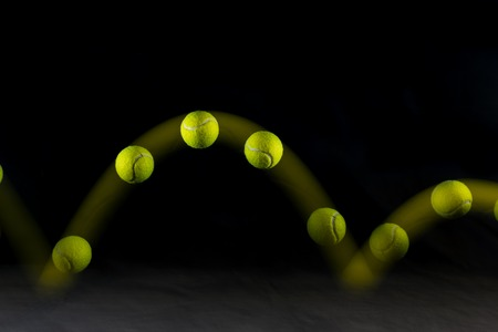 Foto de Movement or bounce of tennis ball isolated on black background. - Imagen libre de derechos