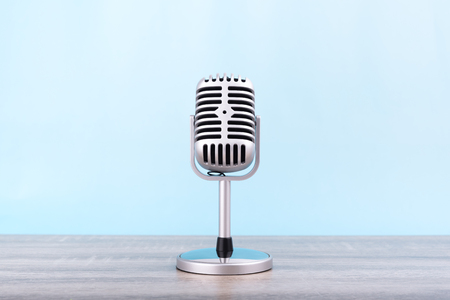 Photo pour Microphone retro Put on wooden table isolated on blue background. - image libre de droit