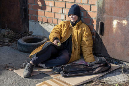 Photo for Homeless woman in a yellow old ragged jacket and blue hat is sitting on cardboard on the pavement and there is an old Apple - Royalty Free Image