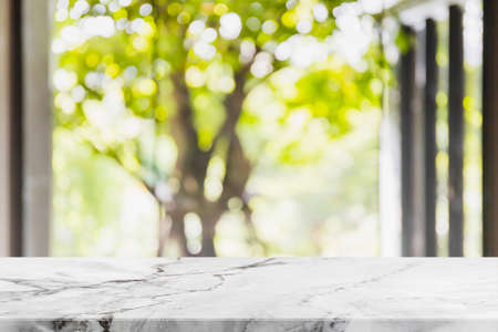 Foto de Empty white marble stone table top and blurred living room in home interior with green tree outside window background. - can used for display or montage your products. - Imagen libre de derechos