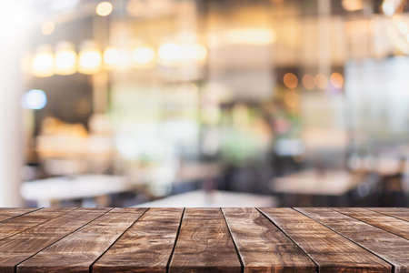 Photo pour Empty wood table top and blurred coffee shop and restaurant interior background - can used for display or montage your products. - image libre de droit