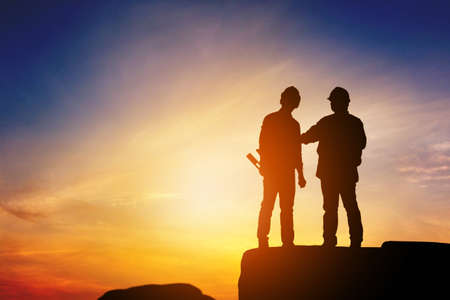Photo pour Silhouette of Engineer and worker standing on stone thinking of project sunset in evening time. - image libre de droit